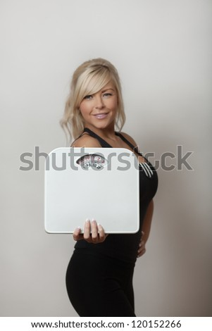attractive woman holding scales to keep an eye on her weight - stock photo