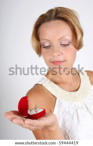 attractive woman holding wedding rings in red box - stock photo