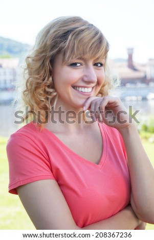 Attractive woman in a pink shirt outside on a river - stock photo