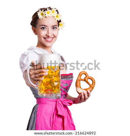 attractive woman in a traditional dirndl with beer and pretzel - stock photo
