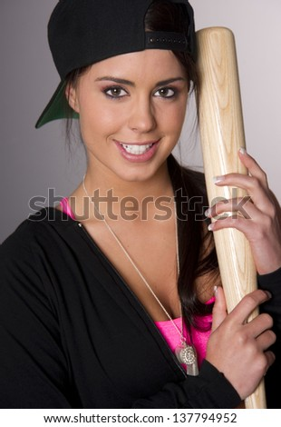 Attractive Woman in Baseball Cap holds her gear
