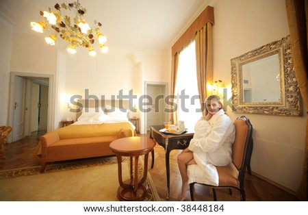 attractive woman in bathrobe in a luxury hotel room