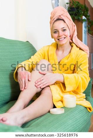 Attractive woman in bathrobe putting cream on legs - stock photo