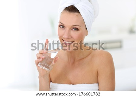 Attractive woman in bathroom drinking water - stock photo
