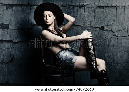 attractive woman in boots shorts and hat sit on chair in old grunge room - stock photo