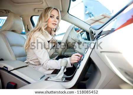 attractive woman in car driver seat adjusting radio - stock photo