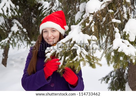 attractive woman in christmas hat near spruce at park - stock photo