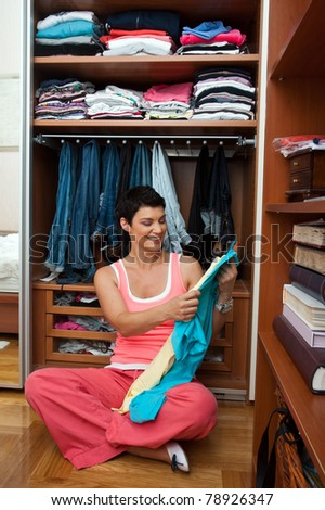 attractive woman in front of closet full with clothes smiling - stock photo