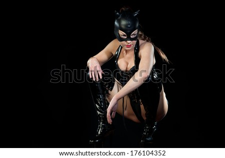 attractive woman in gothic corset dress posing as catwoman