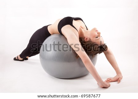 Attractive woman in gym outfit exercising with a ball - stock photo