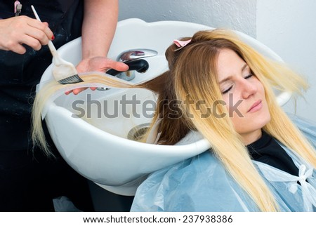 attractive woman in hair salon with coloring foil on her head and washing - stock photo