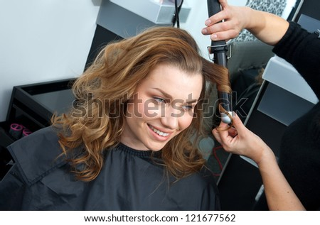 attractive woman in  hairsalon making new hairstyle with hair curler