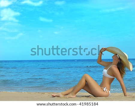 attractive woman in hat sitting on the beach