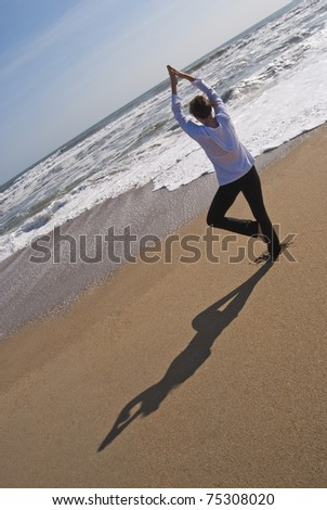 Attractive woman in her 40s doing a yoga tree pose on a secluded beach. Image was taken at the Outer Banks in North Carolina - stock photo