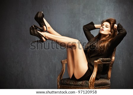 attractive woman in high heels, shorts and black tuxedo jacket sit on chair, cigarette in mouth, long brown hair, small amount of grain added