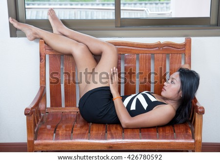 Attractive woman in mini dress resting on a bench. Sexy Asian woman lying on a wooden bench in the room. - stock photo