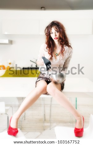 attractive woman in modern kitchen with mixer - stock photo