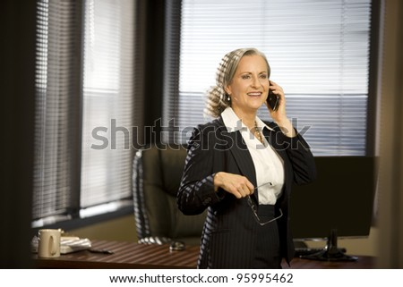 Attractive woman in office talking on cellphone. - stock photo