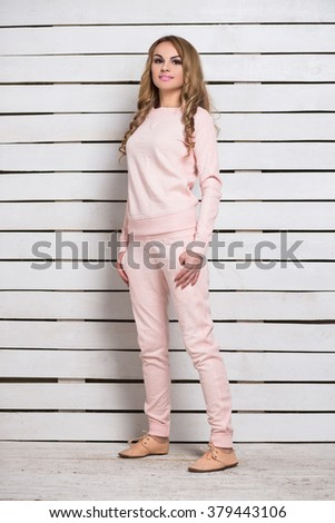 Attractive woman in pink clothes posing near white wooden wall - stock photo