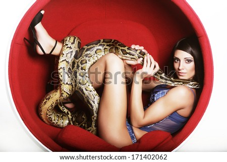 attractive woman in red chair holdung python - stock photo