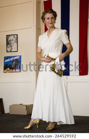 Attractive woman in 1940s clothing posing in front of flag during a reenactment of a World War II fashion show at the Mid-Atlantic Air Museum World War II Weekend, Reading, PA held June 18, 2008 - stock photo