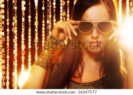 Attractive woman in sunglasses over golden curtains - stock photo