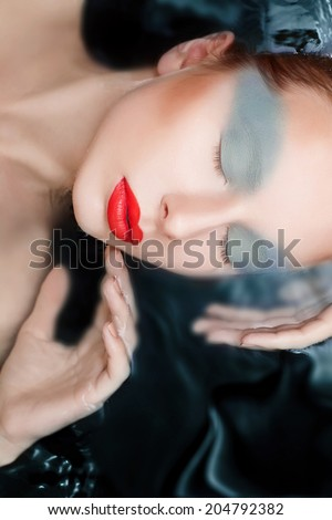 Attractive woman in water with glamor make-up - stock photo