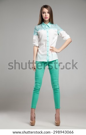 Attractive woman in white blouse and turquoise pants  - stock photo