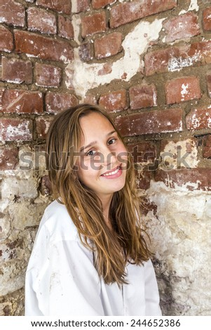 Attractive woman in white shirt with old brick wall background - stock photo