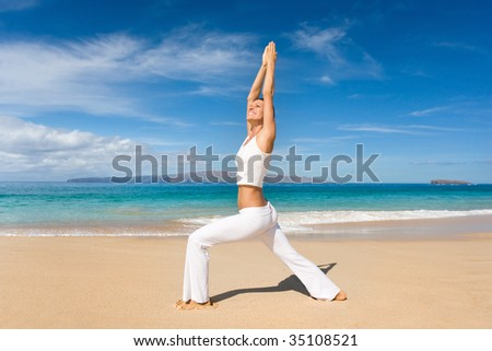 attractive woman in white yoga outfit doing exercise on tropical beach - stock photo