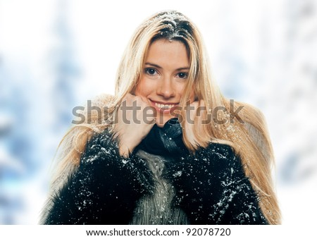 attractive woman in winter clothes covered with snow - stock photo