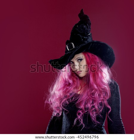 Attractive woman in witches hat and costume with red hair performs magic on a pink background. Halloween, horror theme.