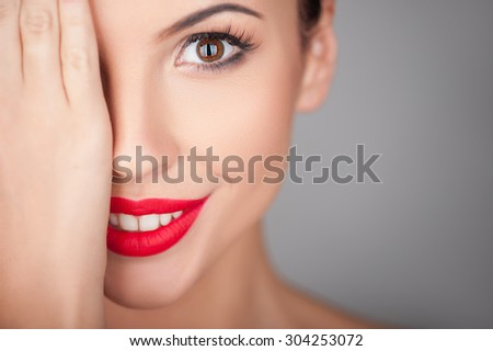 Attractive woman is covering her right eye with her palm. She is smiling and looking forward with joy. Isolated and copy space in right side - stock photo