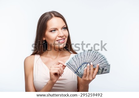 Attractive woman is holding a bunch of money. She is looking aside with happiness. Isolated on background - stock photo