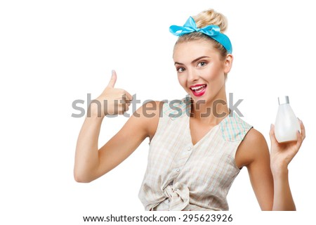 Attractive woman is holding bottle of fluid soap in her hand. She is showing her thumb up and smiling. Isolated on background and there is copy space in left side - stock photo
