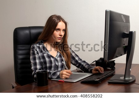 Attractive woman is retouching digital photos operating the computer