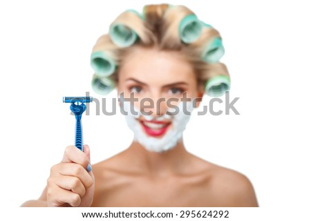 Attractive woman is showing razor to camera and smiling. She has curlers in hair and foam over her face. Focus on razor. Isolated on background - stock photo
