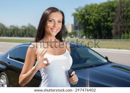 Attractive woman is standing near her new car. She is showing okay sign and smiling. The lady is holding a key of her vehicle - stock photo