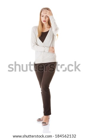 Attractive woman is touching her forehead and stomach, probably is sick. Isolated on white. - stock photo