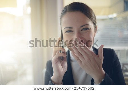 Attractive woman laughing and talking about gossips on the phone - stock photo