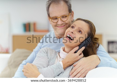 Attractive woman laughing with joy as she takes a call on her mobile phone watched affectionately by her husband