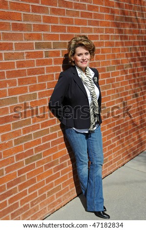 Attractive Woman Leaning Against Brick Wall - stock photo