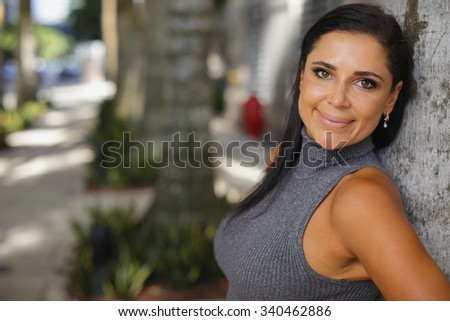 Attractive woman leaning on a tree and smiling - stock photo