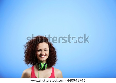 Attractive woman listening to music with headphones on blue background