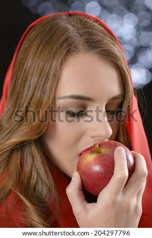 Attractive woman looking at a red apple posing as Eve in the Garden of Eden