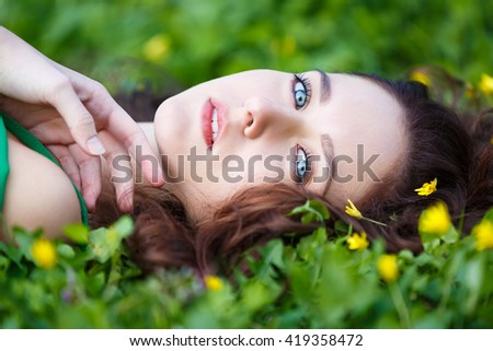 Attractive woman lying in the green grass - stock photo