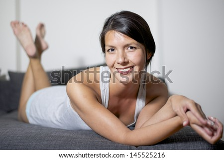 attractive woman lying on lounge sofa and smiling - stock photo