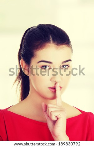 Attractive woman making a keep it quiet gesture - stock photo