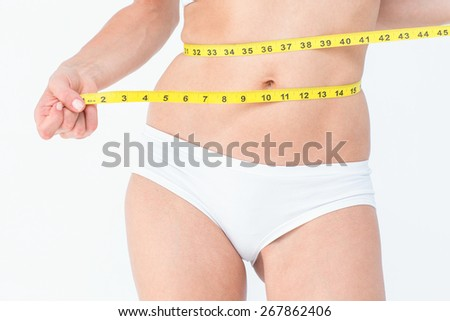 Attractive woman measuring her belly on white background - stock photo