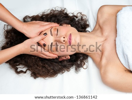 attractive woman on massage table in beauty salon having chiropractic neck adjustment - stock photo